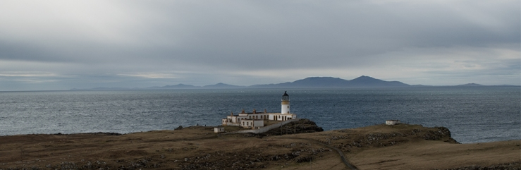 Neist Point lighthouse on west coast of Skye with the Uists on the horizon